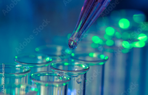 Pipette adding fluid to one of several test tubes - 46595127
