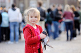 Cute little girl holding a pigeon