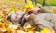 Young smiling woman lying on leaves in autumn