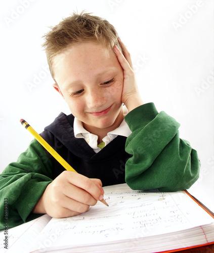 Niño estudiando, escribiendo,sentado en un pupitre.escolar.