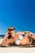 Attraktive Frau im Bikini liegt in Sonne am Strand