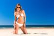 Attraktive Frau im Bikini kniet in Sonne am Strand