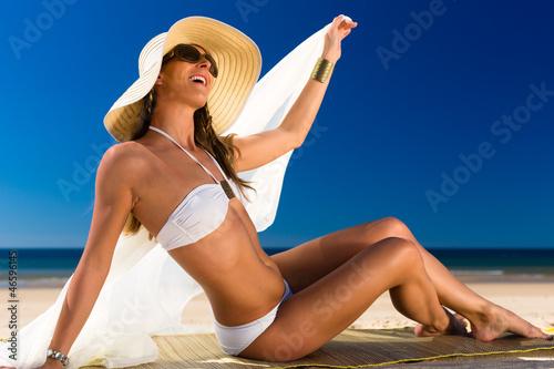 Attraktive Frau im Bikini lacht die Sonne am Strand an