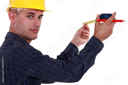 Tradesman using a measuring tape