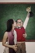 Boy raising trophy kiss by his mother in class
