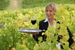 Smiling waitress with wine in a vineyard