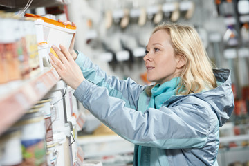 woman shopping paint at hardware store