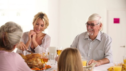 Happy father carving turkey at head of table