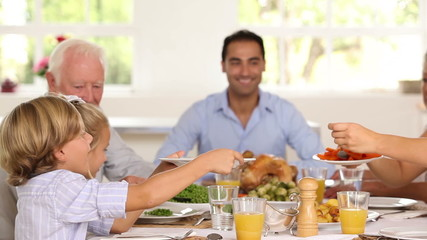 Mother serving up carrots for son at family dinner