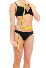 Slim female body with measure tape around waist.