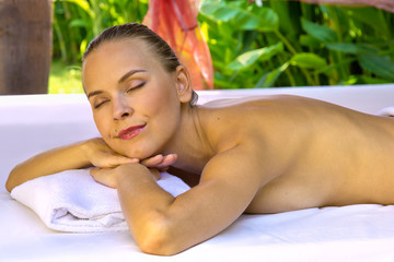Smiling pleased female enjoys in spa.