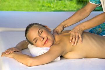 Smiling female enjoys in massage.