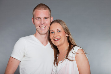 Young couple together in love against grey wall. Studio shot.