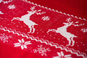 Real red knitted background with white Christmas deers and snowf