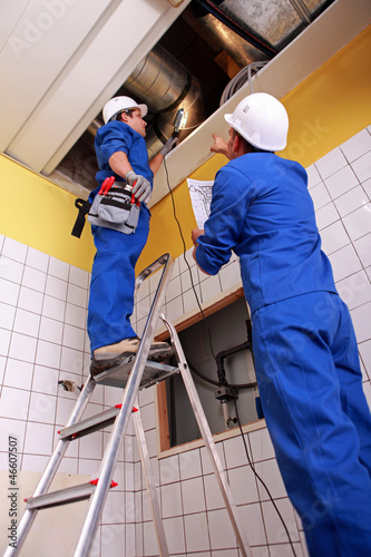Man and woman repairing ventilation system