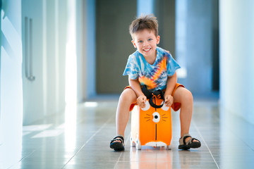 Cute happy boy with a suitcase at airport
