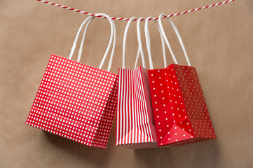 Red gift package paper bags hanging on a ribbon. Old brown paper