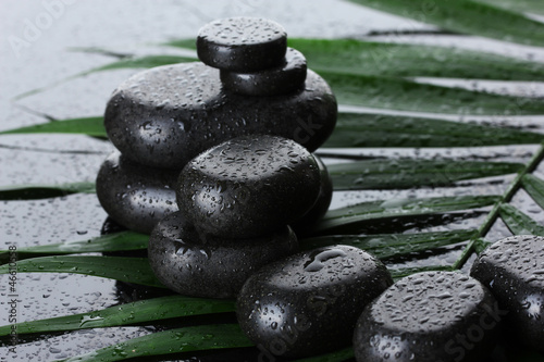Spa stones with drops on green palm leaf on grey background