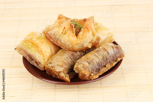 Sweet baklava on plate on bamboo mat