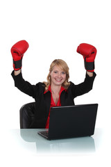 Businesswoman sat wearing boxing gloves