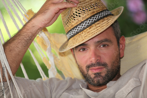 Man relaxing in hammock whilst on holiday