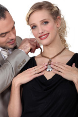 husband offering his wife a necklace