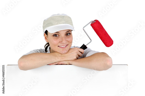 Female decorator with a roller and a board for message
