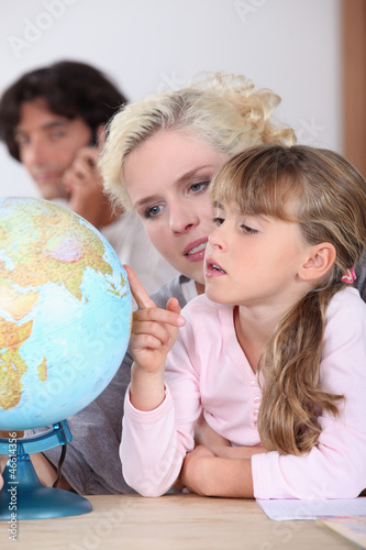 mother is showing to her daughter some country on a globe
