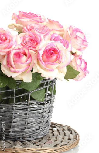 beautiful bouquet of pink roses in wicker vase, isolated