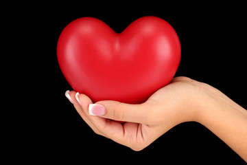 Red heart in woman's hand, on black background close-up