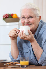 Elderly lady enjoying cup of tea