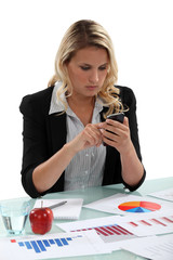 A businesswoman texting with charts on her desk.