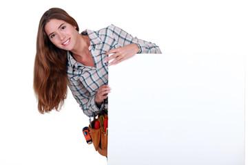 Female carpenter holding white sign for message