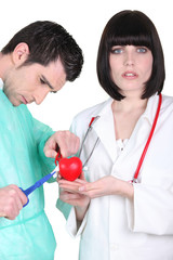 Doctors with plastic heart
