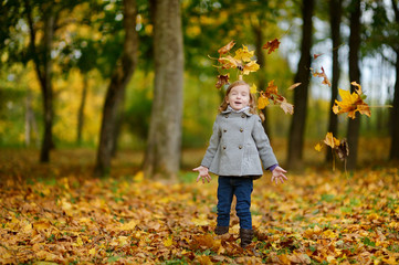 Adorable girl having fun on an autumn day