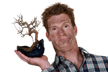 Smoke faced man holding a burnt bonsai