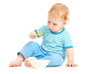 child or kid eating from plate with spoon