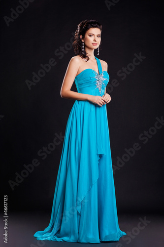 Cute young woman in fashion classic blue dress on black