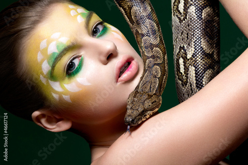 Beautiful young woman with a snake (python) - circus performance