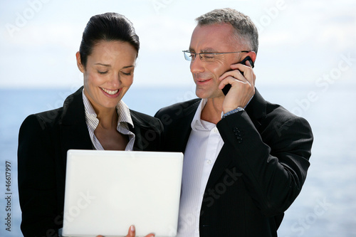 Businesspeople outdoors with laptop
