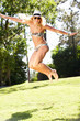 Woman Wearing Bikini Jumping In Garden