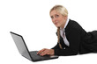 Blond businesswoman laying on front and typing on laptop