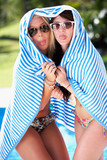 Two Women Wrapped In Towel Standing By Swimming Pool