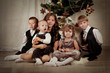 Five children are sitting around the Christmas tree