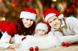 Christmas family  in red hats. Happy parents and baby