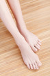 Well-groomed female feet on wooden floor