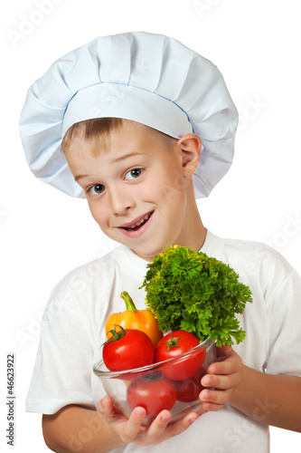 cook boy Chef is holding fresh vegetables