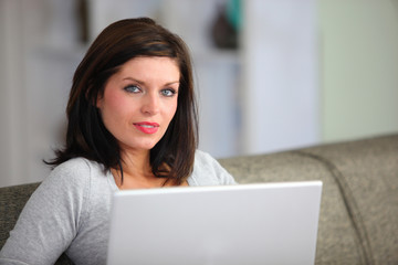 Woman with computer sitting on sofa