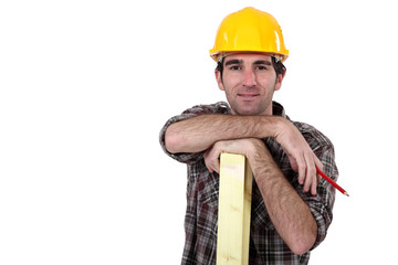 Construction worker posing with a wooden plank