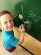 Niño regreso a clases dibujando en un pizarrón.